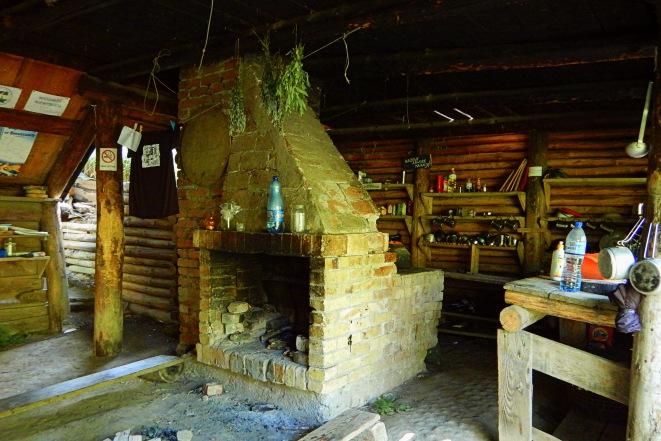 Kominek a za nim kuchnia na bazie w Lopience. Bieszczady z jaktoblisko.com